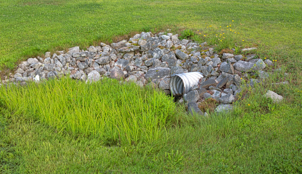 A stainless steel drainage culvert surrounded by rocks and green grass.  Effective drainage will have huge impacts on the health of your lawn and landscape.