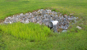 A stainless steel drainage culvert surrounded by rocks and green grass.